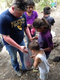 Sociology Instructor Daniel Brewster shares candy with Nicaraguan children