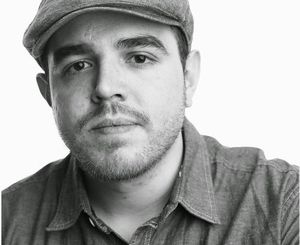 Black and white photo of poet José Olivarez wearing a hat