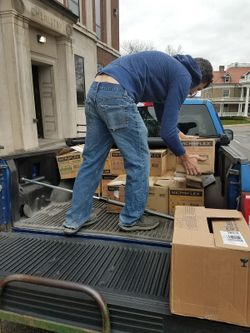 Program assistant Kevin Dixon loads boxes of personal protective equipment into a pickup truck