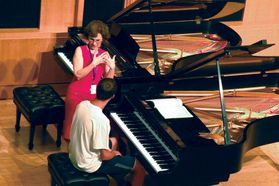 student sits at piano while instructor stands and speaks next to him
