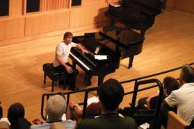 student turns to audience after finishing playing piano
