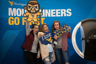 Three female prospective students pose with WVU-themed props in the Mountaineers Go First photo booth