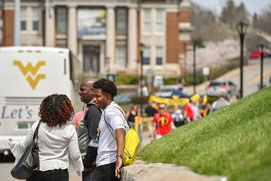 Parents and student wait in front of the Mountainlair Student Union with a WVU bus and Oglebay Hall in the background