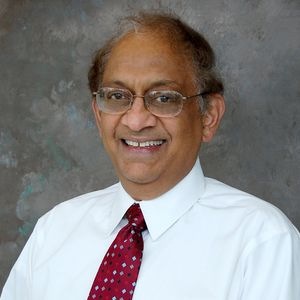 A portrait of Hota Gangarao wearing a white dress shirt and red tie