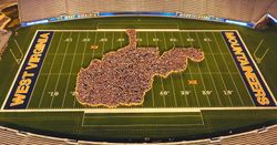 Members of the class of 2021 and the WVU marching band form the shape of West Virginia