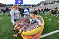 A student sits on top of inflatable donuts on Mountaineer Field