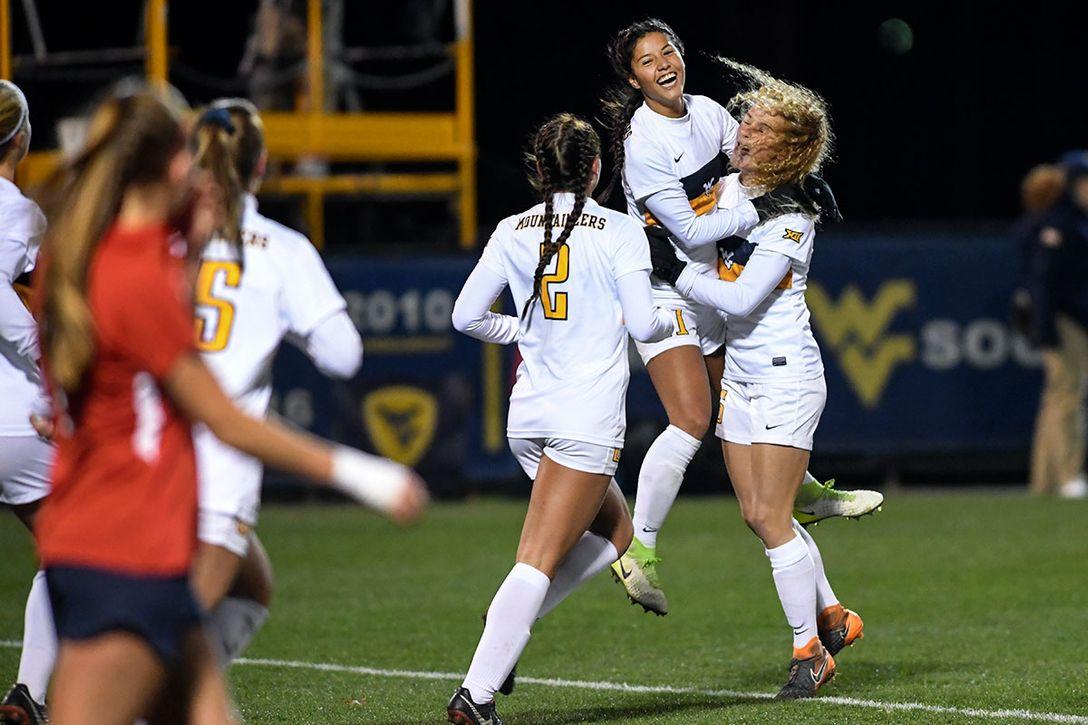 Women's soccer players embrace in celebration