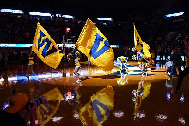 Cheerleaders carry WVU flags during pregame in darkened Coliseum