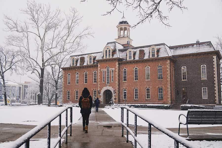 walking in the snow in front of Martin Hall
