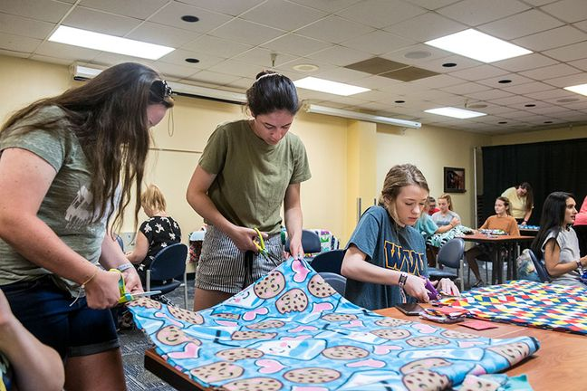Students cut fleece blankets for Project Linus