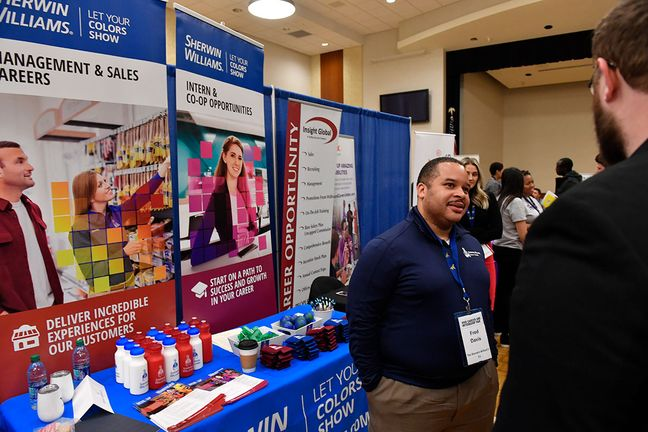 Sherwin Williams representative talks to a student at a career fair