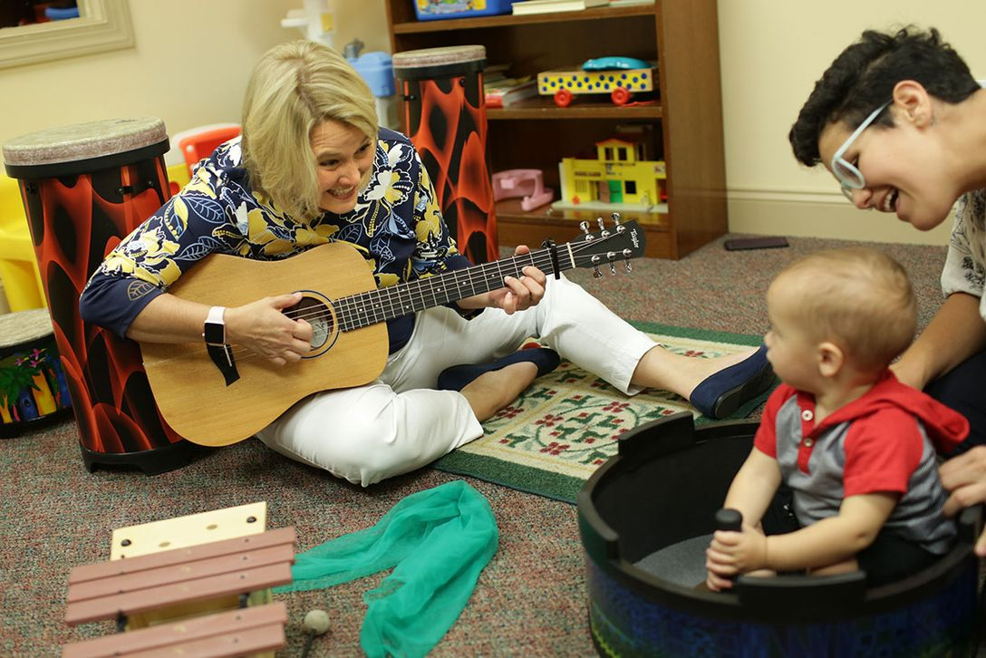 Music therapist Dena Register plays with, and sings to, a child at the Center for Excellence in Disabilities