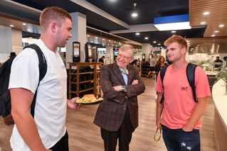 President Gee talks with two students as they get their meals at Hatfields