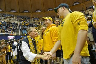 President Gee shakes hands with students.