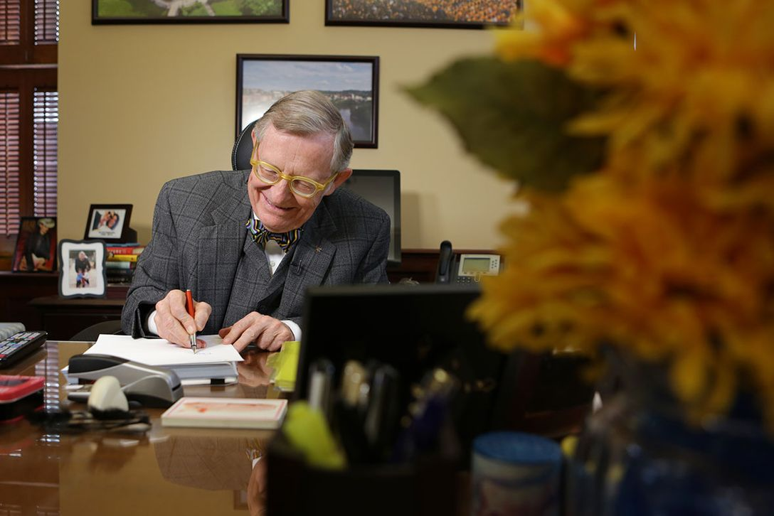 President Gee sits at his desk writing a letter