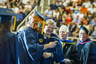 President Gee with graduate wearing a mask