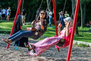 Nadia Fazli and Nur Abdullah swing on a swing set at White Park.