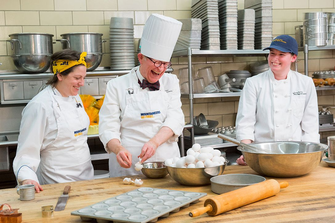 President Gordon Gee assists Barbara Yanera and Cassie Heaster with baking a cake in the Towers kitchen