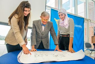 President Gee and two students review plans.