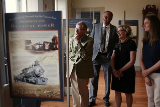 President Gee and members of the WVU group view displays about Beverly's history.