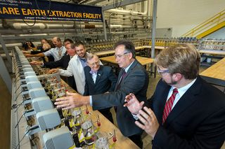 President Gee and other tour members interact with laboratory equipment
