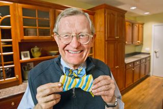 President Gee holds up a gold and blue bow tie cookie