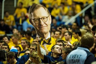 Student holds up a President Gee cut-out at a basketball game.