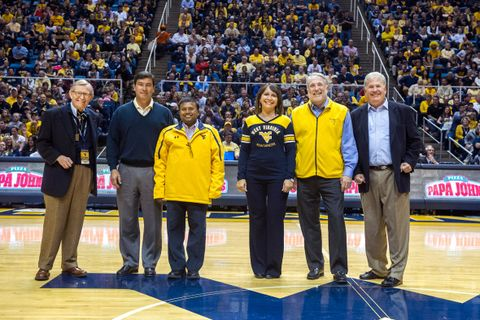 President Gee stands on the Coliseum floor with 2014 Distinguished Alumni inductees.