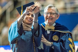 An Eberly College graduate takes a selfie with President Gee