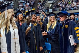 President Gee congratulates a group of Eberly graduates