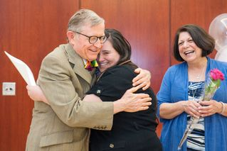 President Gee hugs Milda Mullins as Provost Joyce McConnell looks on.