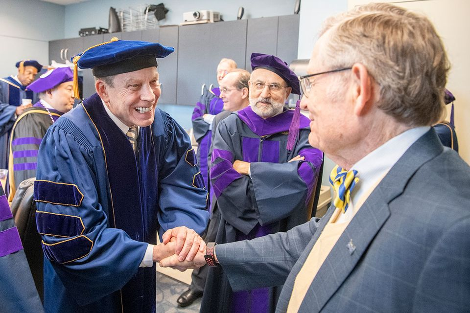 Robert Fitzsimmons shakes hands with President Gee