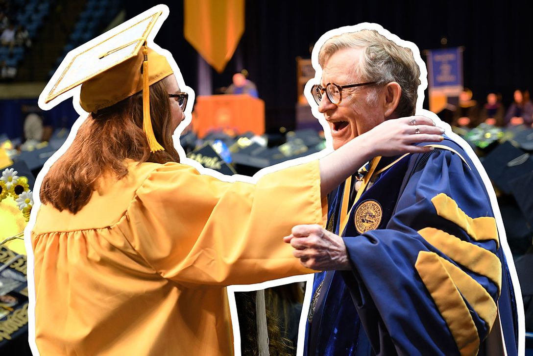 President Gee reaches to hug a graduate wearing a gold cap and gown