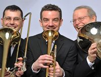 Members of NY Brass Arts Trio holding horn instruments