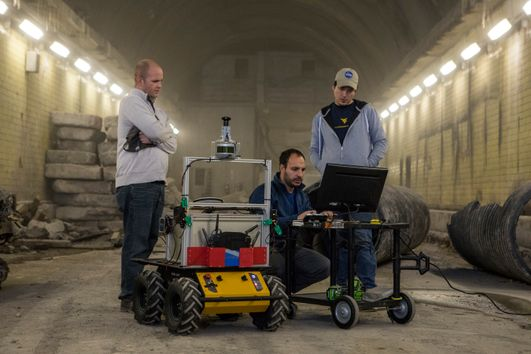 International students working on a robot in an underground corridor.