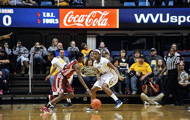 Coca-Cola branding on a digital marque during a women's basketball game.