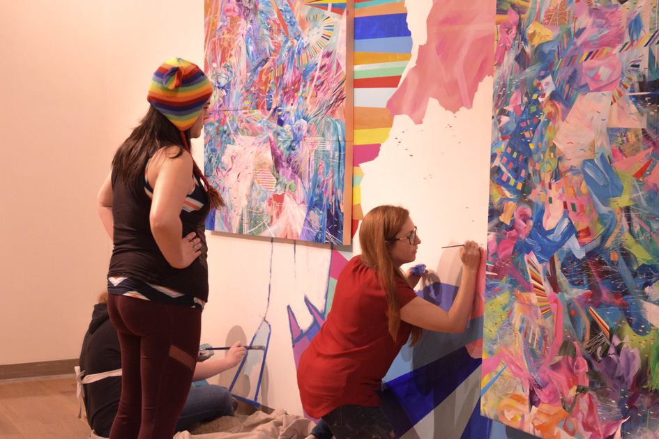 Amy Schissel working on mural with student