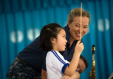 Kelly Cartwright watching a child use a conducting baton
