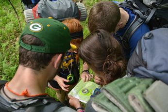 A group of Adventure WV participants gathered around a map