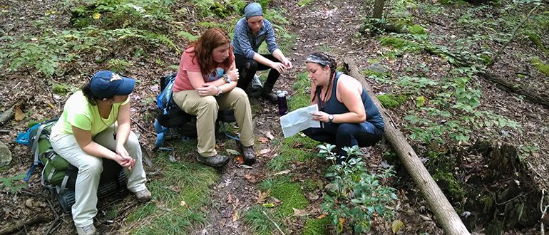 a group of female hikes look at a map during a backcountry hike