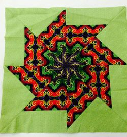 quilt block with light green border, black purple green and red center