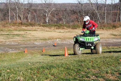 A youth rides their ATV on a course.