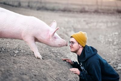 Teen nose to nose with a pig