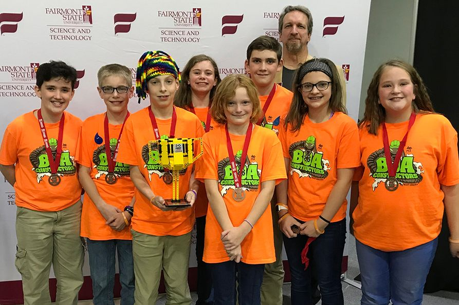 Members of Monroe County 4-H robotics team pose with state championship trophy