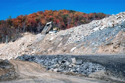 A dump truck unloads a load of fill from a mine site.