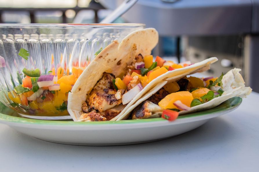 Two fish tacos with peach salsa on plate.