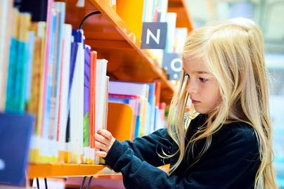 young girl choosing a book from the library shelf