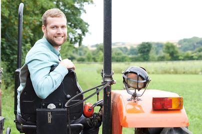 young male farmer on an orange tractor turning around to face camera smiling