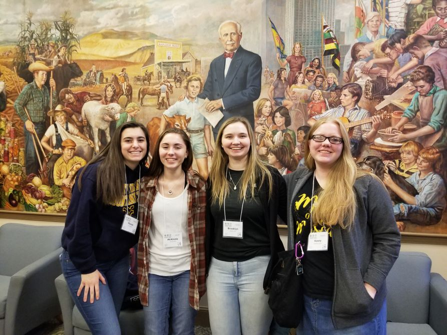 Four youth 4-H girls stand in front of a painting at the National 4-H Conference Center