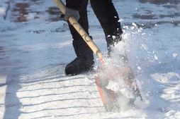 person pushing snow shovel to clear snow